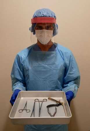 Sterile Processing Technician holding a tray full of instruments in full scrubs. Technician preparing for certification while performing hands on training.